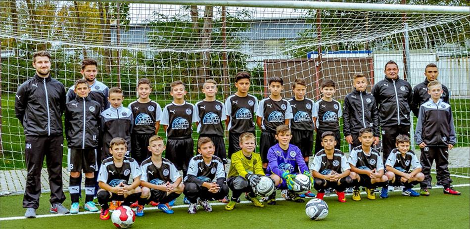 Trainer und Jungenmannschaft des SG Wattenscheid 09 posieren vor einem Fußballtor.