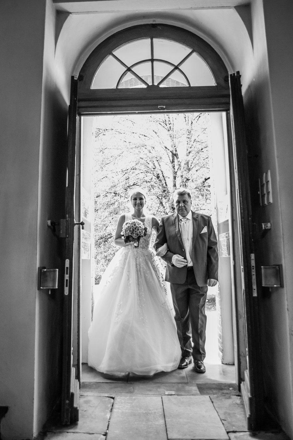 Die Braut wird von Ihrem Vater in die Kirche begleitet