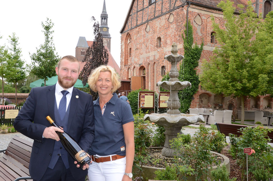 Lukas Dickmann und Melanie Busse mit einem ganz besonderen Wein von der Mosel vor dem Hotel Schloss Tangermünde.