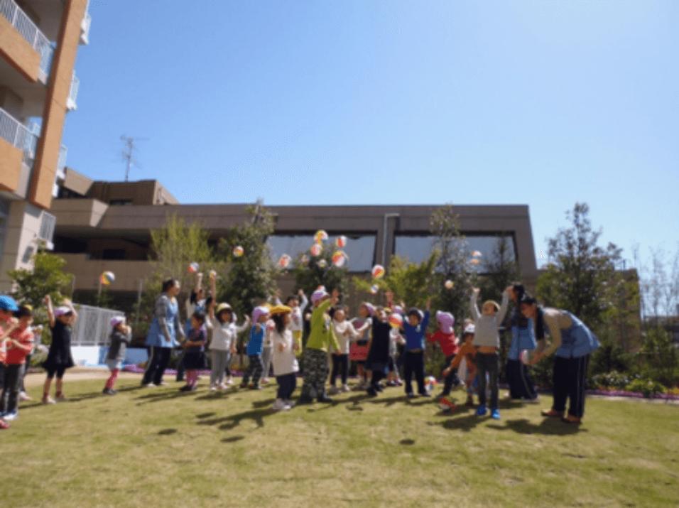 広い園庭で遊ぶ子どもたちと保育士