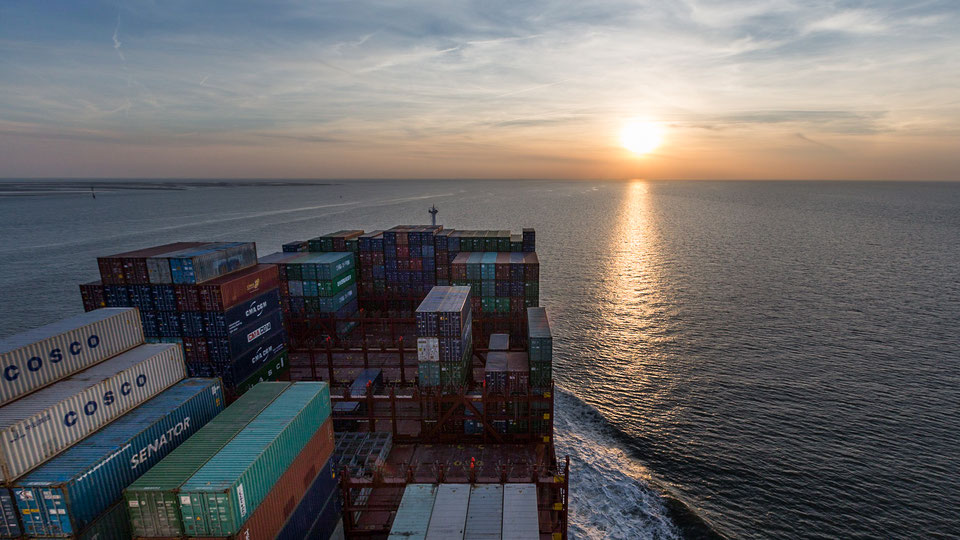 On board a container ship on Elbe river towards sunset