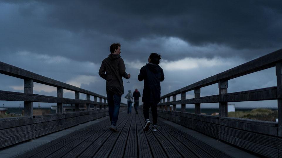 Two couples walking Seebrücke Heiligenhafen