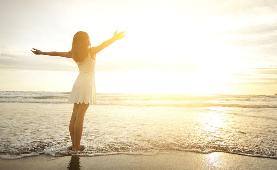 海辺で明るく眩しい朝日に向かって両手を広げる女性