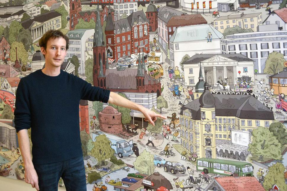 Der Illustrator Hannes Mercker zeigt auf Details seines Stadt-Wimmelbildes