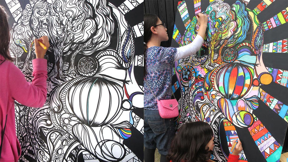 Members of he public colouring this interactive wall mural.