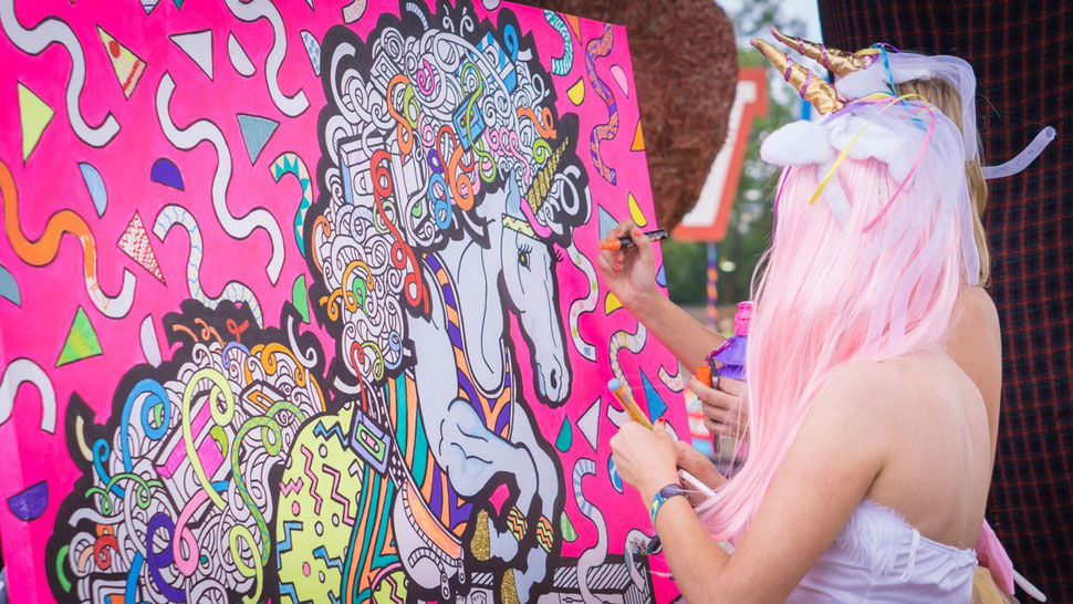 Two unicorns colour in a giant unicorn canvas at a festival