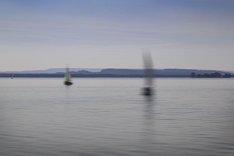 Segelboote auf Wasser mit Land im Horizont