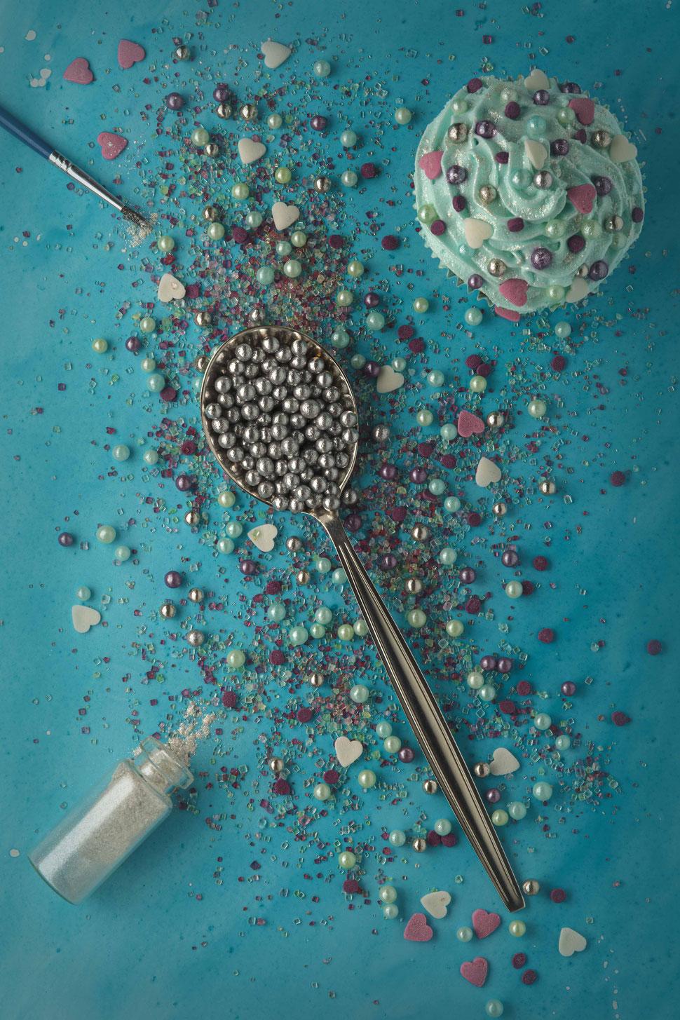 Löffel gefüllt mit silbernen Zuckerperlen und buntem Muffig