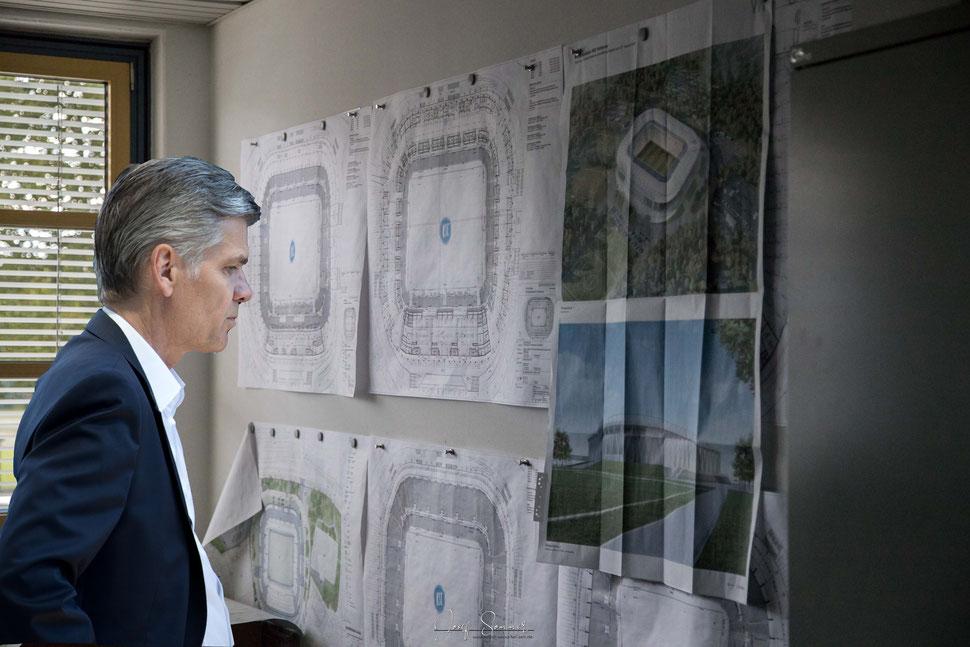Ingo Wellenreuther studiert die Baupläne des neuen Wildparkstadions (Fotomontage)