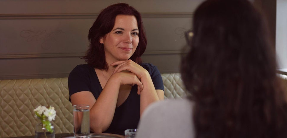 Conny, Mindset-Coach für Frauen, hört einer Klientin aufmerksam in einem Café zu.