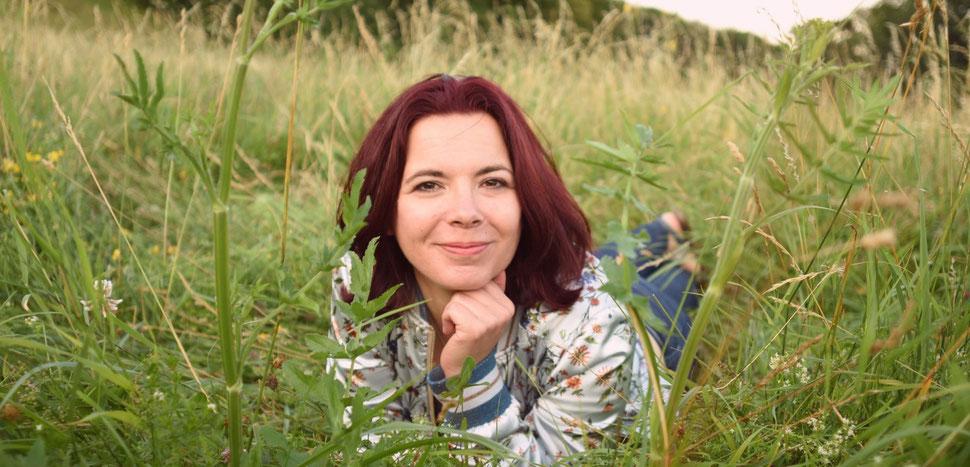 Conny, Mindsetcoach für Frauen, liegt entspannt auf einer Wiese und lächelt verschmitzt in die Kamera.
