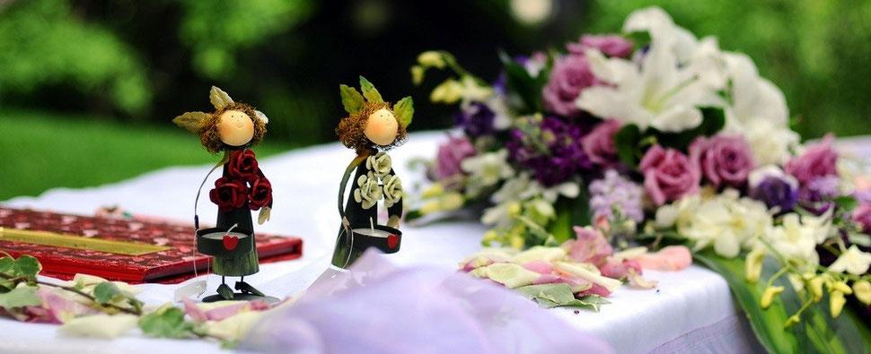 Kerzenhalter-Männchen auf mit Blumen geschmückten Trautisch bei einer freien Trauung im Freien