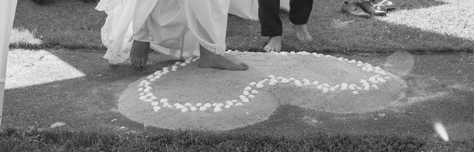 Brautpaar tritt bei einer freien Trauung zum Jawort in ein Herz aus Sand – Foto von Michele Albrecht