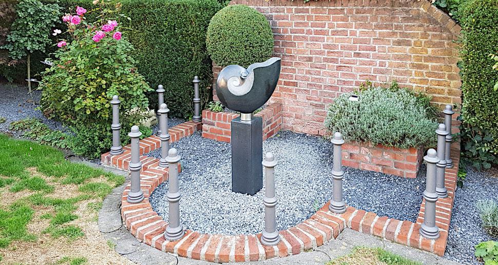 Gartengestaltung aus Naturstein. Schwarze Nautilus auf einem schwarzen Steinsockel als Gartengestaltung.