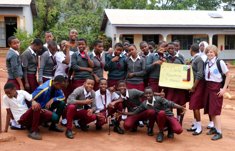 Gruppenbild von Schülerinnen und Schüler der One World Secondary School Kilimanjaro, die sich mit einem Plakat für die Spende der Kreuzkirche München bedanken.