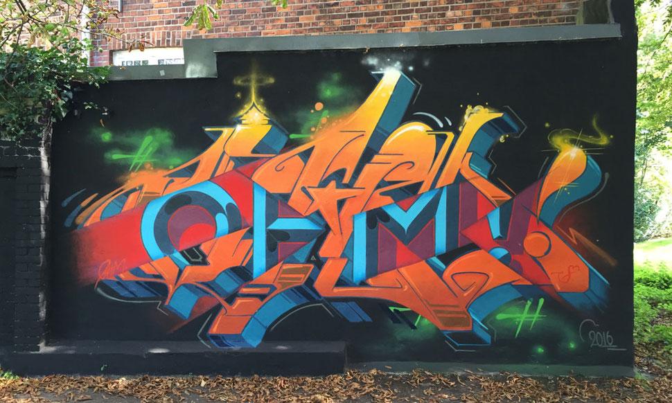 Auf einer Fassade steht in großen gelb und orangen Graffiti Buchstaben der Name Ohm. Der Schrift ist zerschnitten und man sieht in einer grotesken Schrift die Buchstaben OHM durchblitzen.
