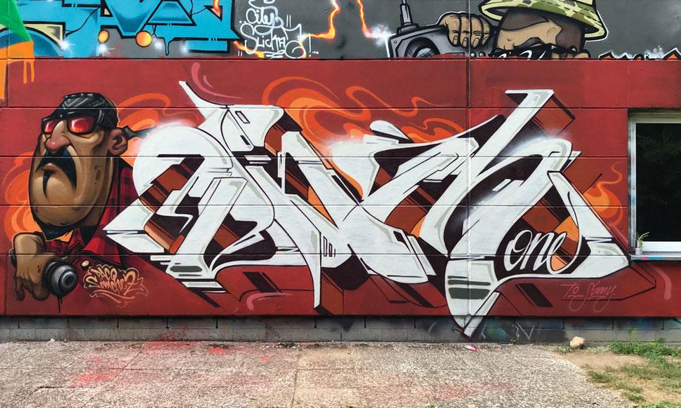 Auf einer orange roten Wand ist ein weiße Graffiti zu sehen. Daneben ein Charakter von Paco Sanchez – ein Latino mit Sonnenbrille, einem rot schwarzem Karohemd und einer Sprühdose in der Hand. In großen Buchstaben steht der Name Ohm One.