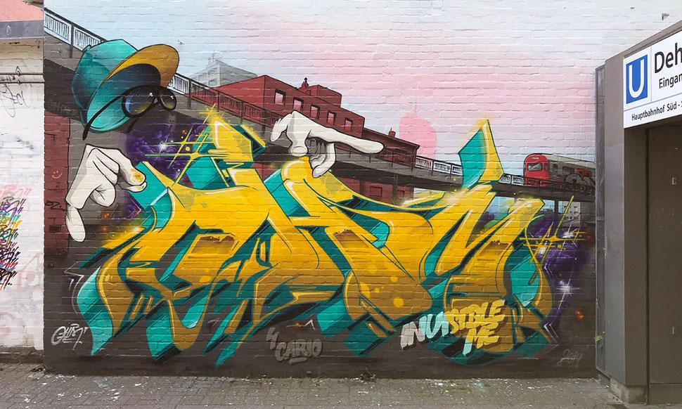 """Vor dem Aufgang der U-Bahn Dehnhaide steht in großen gelben Graffiti Buchstaben der Name """"Ohm"""". Im Hintergrund des Graffiti ist der Stadtteil Barmbek zu sehen. Mit der Trasse auf der eine  U-Bahn fährt. Über den Buchstaben schwebt ein """"Unsichtbarer""""."""