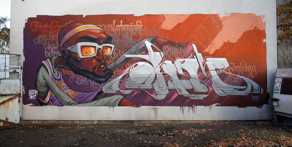 Auf einer Fassade steht in großen grauen Buchstaben der Name Ohm, auf einem orange lila Skyline. Daneben ist ein Charakter, ein Basketball Spieler mit Sonnenbrille, von Paco Sanchez zu sehen.