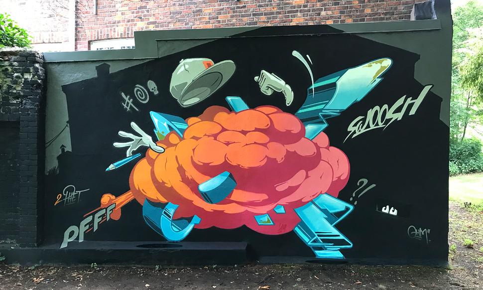 Auf einer Wand ist eine farbenfrohes Graffiti zu sehen. In großen Buchstaben steht der Name Ohm und im Vordergrund stehen alte Citroens. Mitten in Hamburg Barmbek.