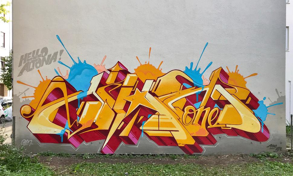 Auf einer Fassade steht Hello Altona, darunter ist eine gelbes Graffiti. Es steht in großen gelben Buchstaben der Name Ohm One. Im Hintergrund sind bunte Farb Splashes zu sehen.