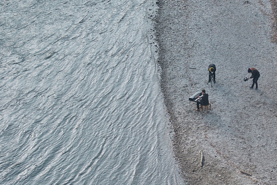 The image shows the aerial photograph of a piano player on the shore of the Aare river in Bern. There are two men filming the piano player.