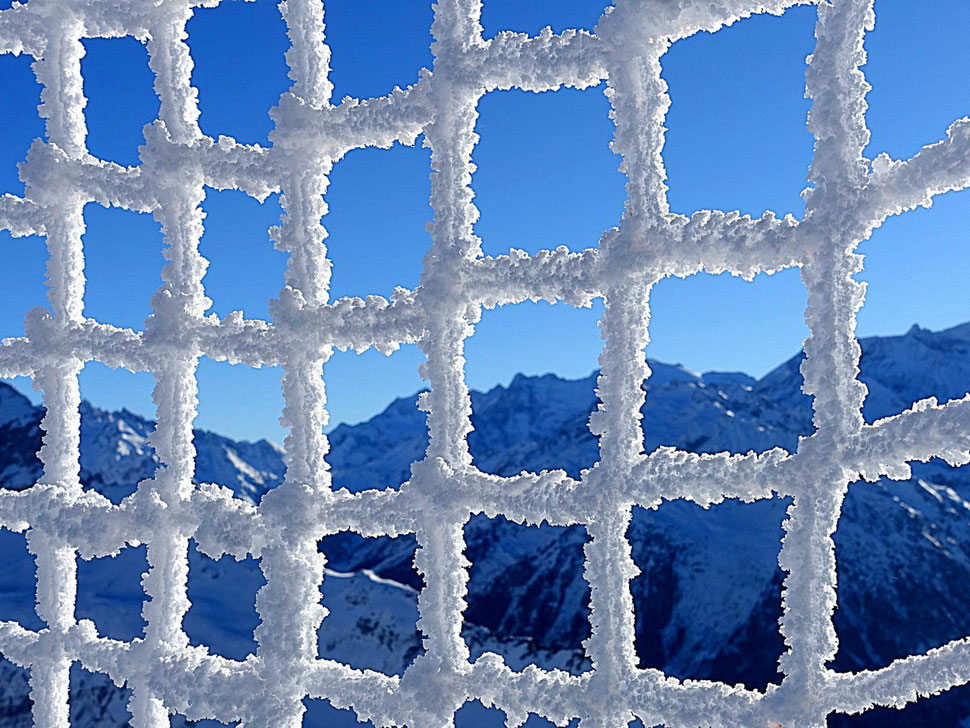 The image shows the photography of a snow covered safety net with some mountains and a snippet of blue skies in the background.