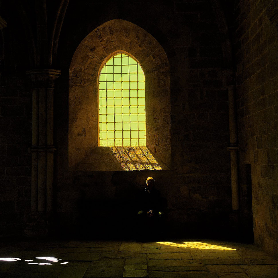 The image shows the photograph of a man sitting below a church window. The sun throws a yellow light an the hair of the man; his face is not visible.