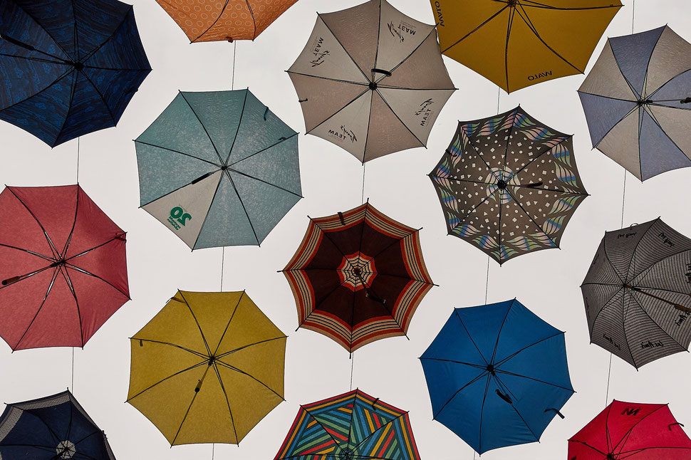 The image shows the photograph of colorful umbrellas from below.