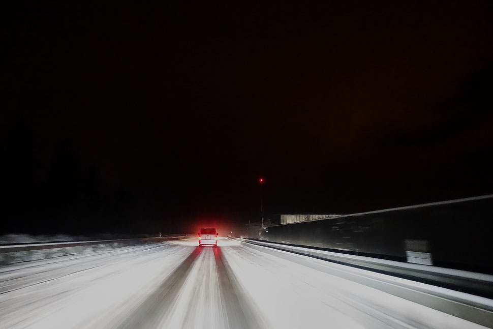 The image shows a photo of a snow covered street with crash barriers on both sides and a single car from behind.