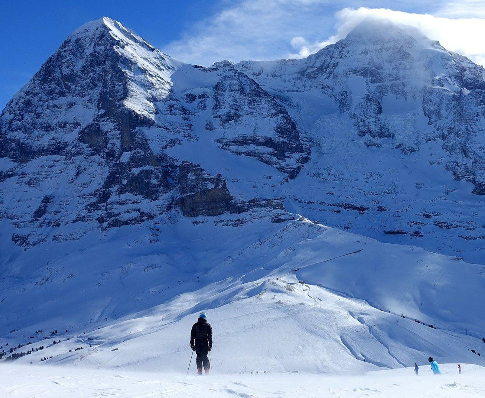 The photograph shows an image of a skier in the foreground and of the impressive north face of the Eiger in the background.