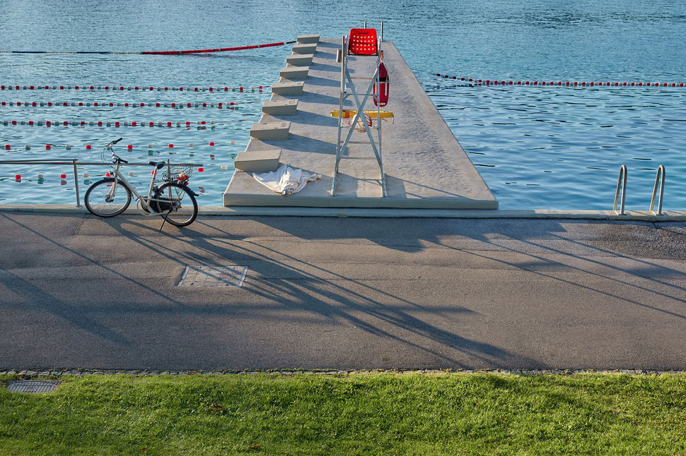 The image shows the photograph of a summer evening in an empty public swimming pool.