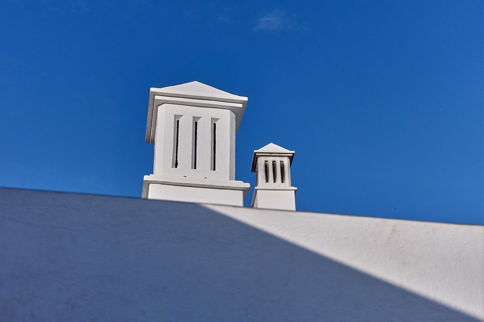 The image shows the photograph of a white wall and two chimneys agains the bright blue sky.