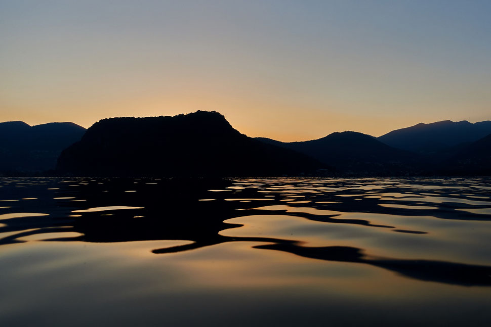 The image shows the photograph of light and shadow patterns in the water of Lake Lugano. It is after sunset and you can see the dark shapes of mountains in the background.