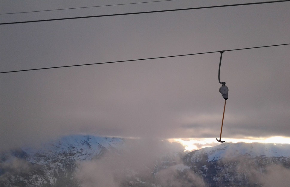 The photograph shows an image of a single ski lift ironing against the backdrop of mountains, clouds and a shimmer of sunlight.