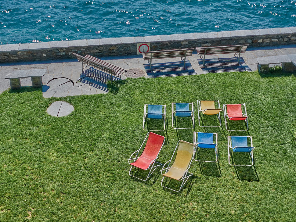 The image shows a photograph of 8 deck chairs with different colors on a lawn and three benches near the shore of a lake.