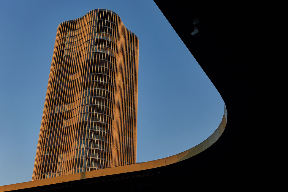 The image shows the photograph of a snippet of a high-rise building and part of the roof of Lucerne's football stadium. The high-rise building is illuminated by late afternoon sunlight.