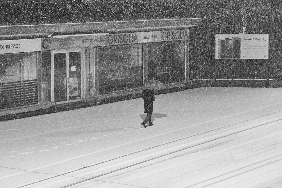 The image shows the photograph of a man with an umbrella walking on a snow covered street. There is a storefront next to him.