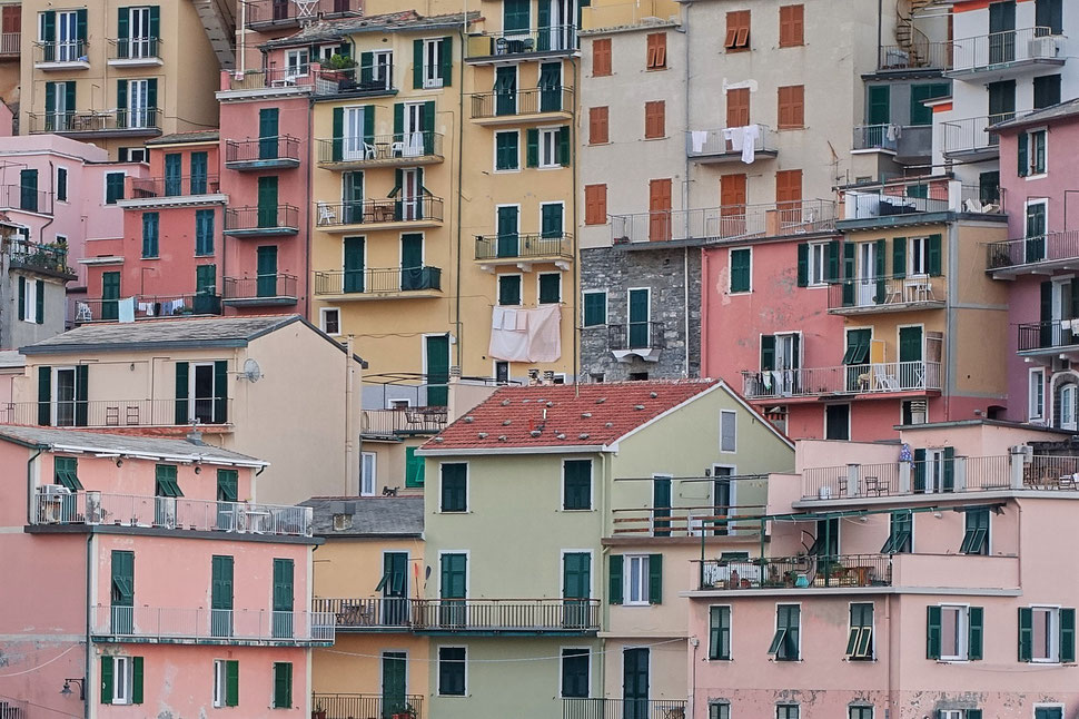 The image shows a photograph of the colorful façades of Manarola, a small village in Italy.