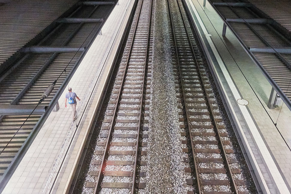 The image shows the photograph of an aerial view of a man wallking along train tracks at a train station late at night. The platform is empty.