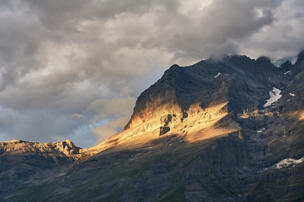 The image shows the photograph of mountain that is illuminated by evening sunlight against a clouded sky.