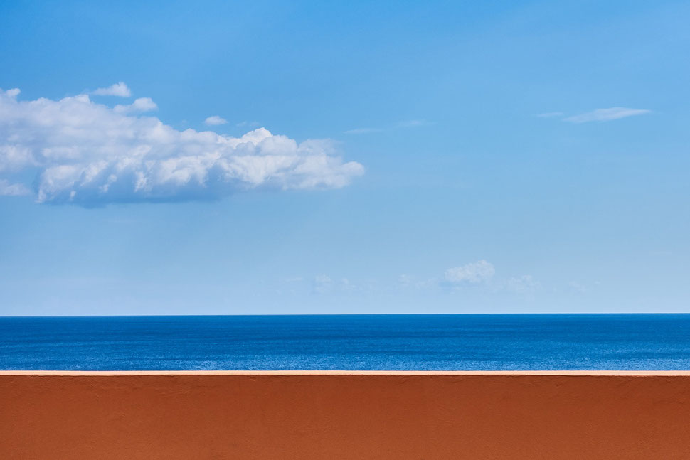 The image shows the photograph of a brown wall against the background of the dark blu sea and light blue sky with some clouds.