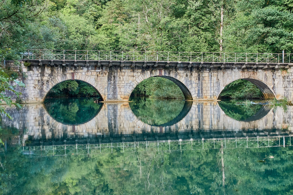 The image shows the photograph of a bridge with three arcades crossing a river. The bridge is reflected in the still water of the river.