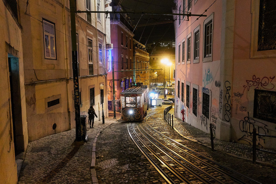 The Image shows a photograph of a street and a tram in Lisbon by night.