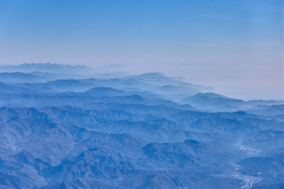 The image shows the aerial photograph of mountain ranges partly covered in fog.