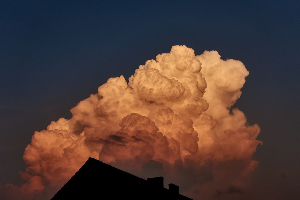 The imag shows the photograph of a massive cloud lit by evening light against a dark blue sky.