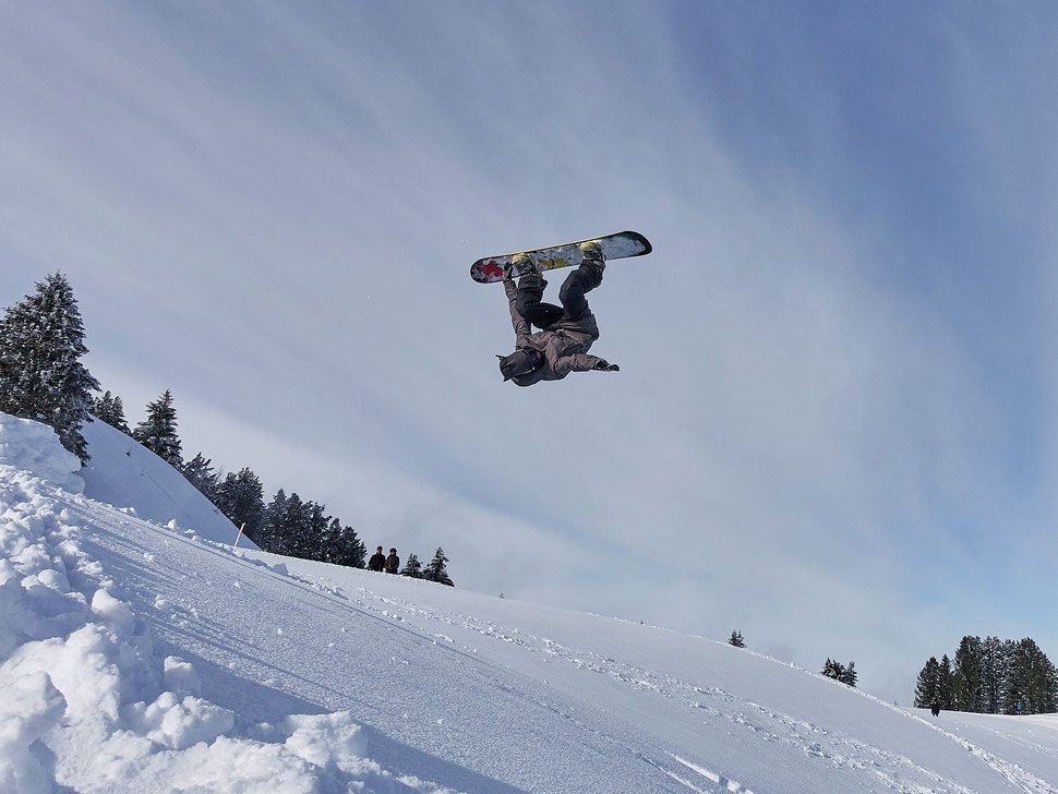 The image shows a photograph of a snowboarder in the air doing a back flip.