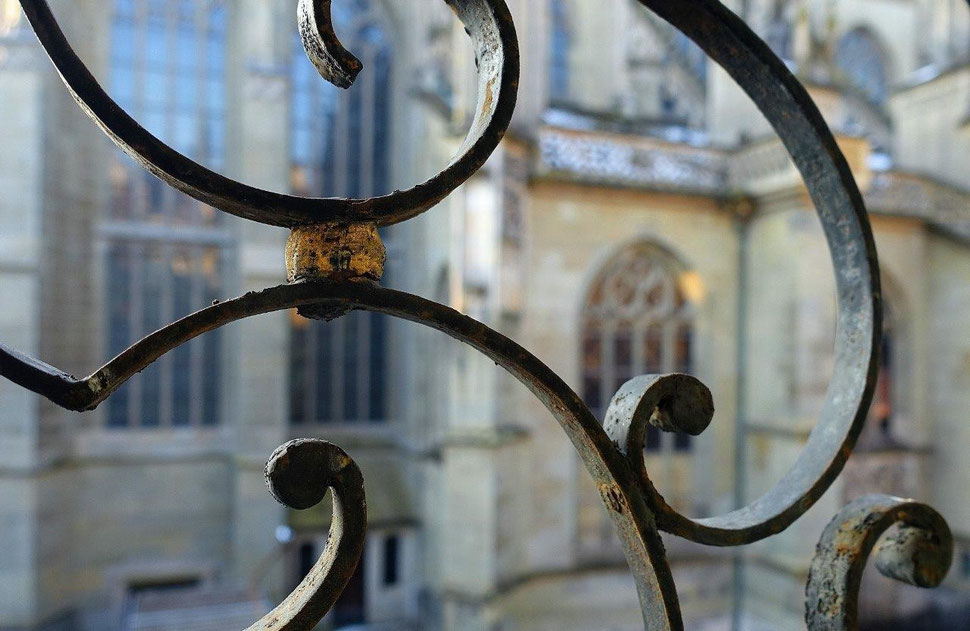 The photograph shows an image of wrought iron window grilles in the foreground and the walls and windows of the bernese cathedral in the background.  Bild von Bern.