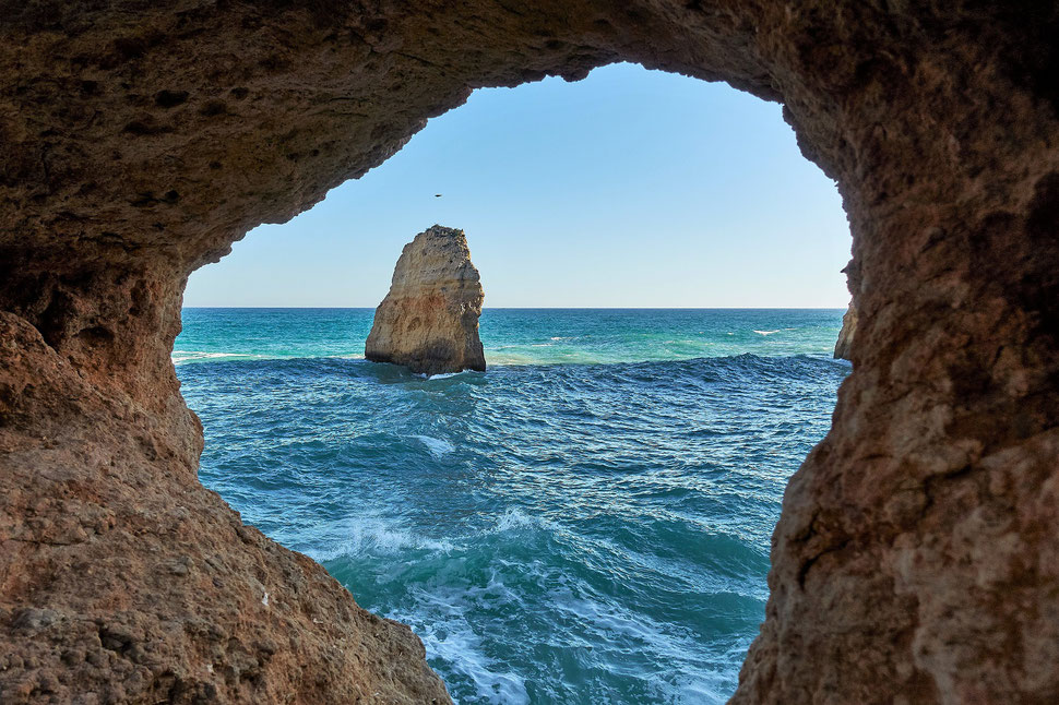 The image shows a photograph of a cliff hole through which you can see the sea and a protruding rock.