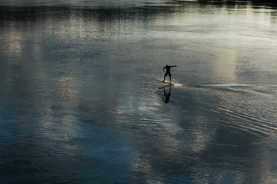 The image shows the photograph of a wind turbine from below against the backdrop of a blue sky with white clouds.